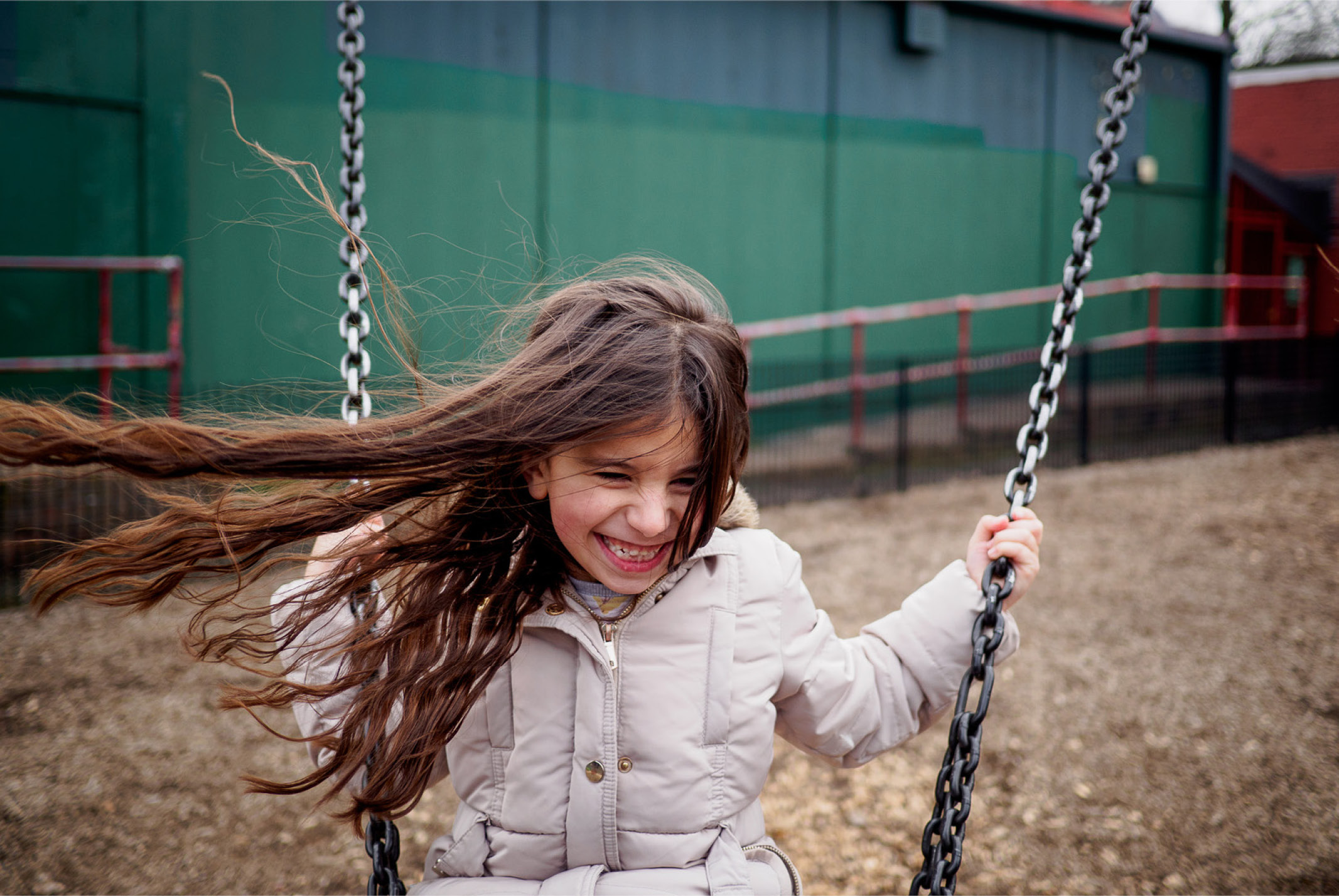 Little girl on a swing smiling happily in Tooting Common