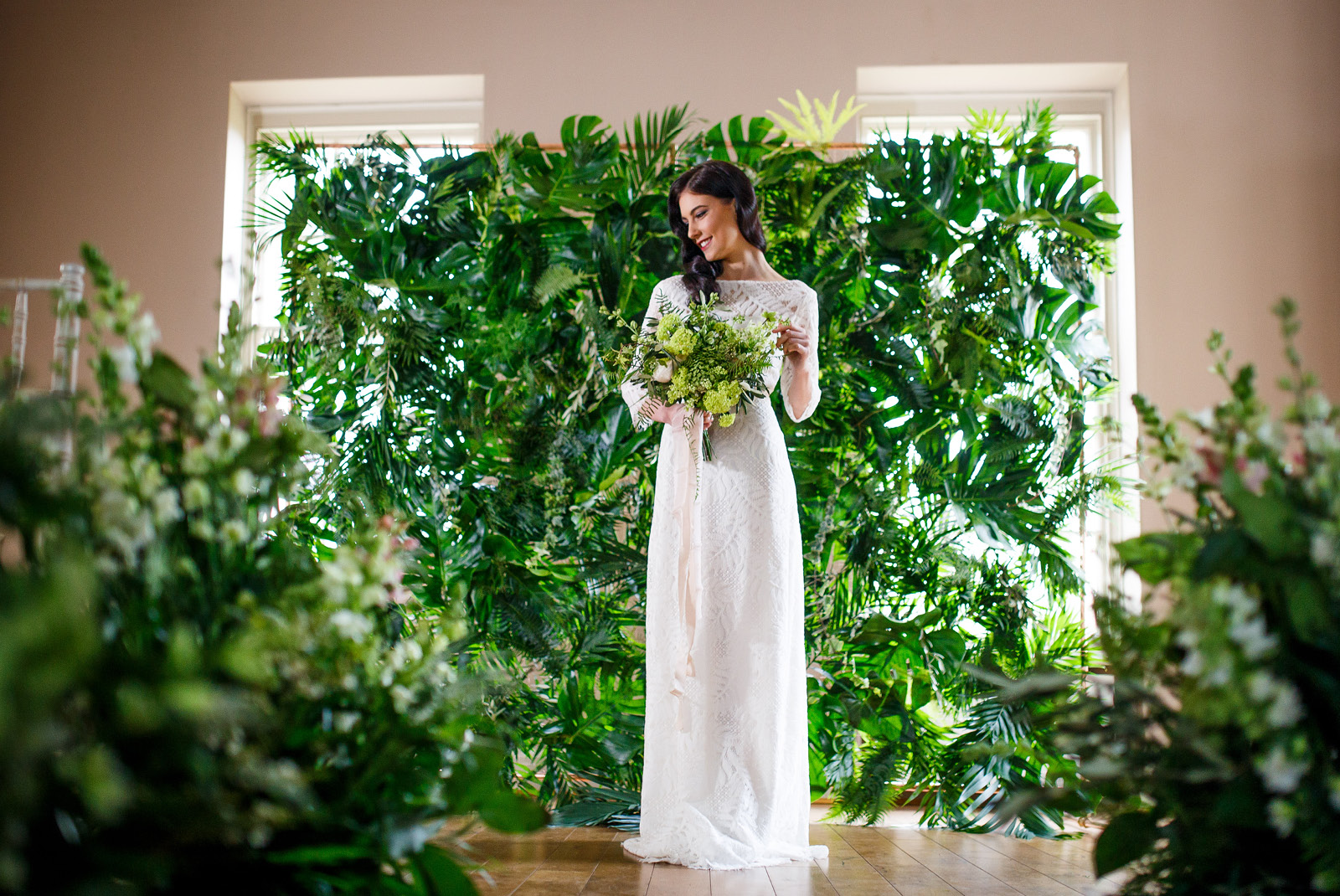 Bride standing in front of a greenery wall with a bouquet of flowers