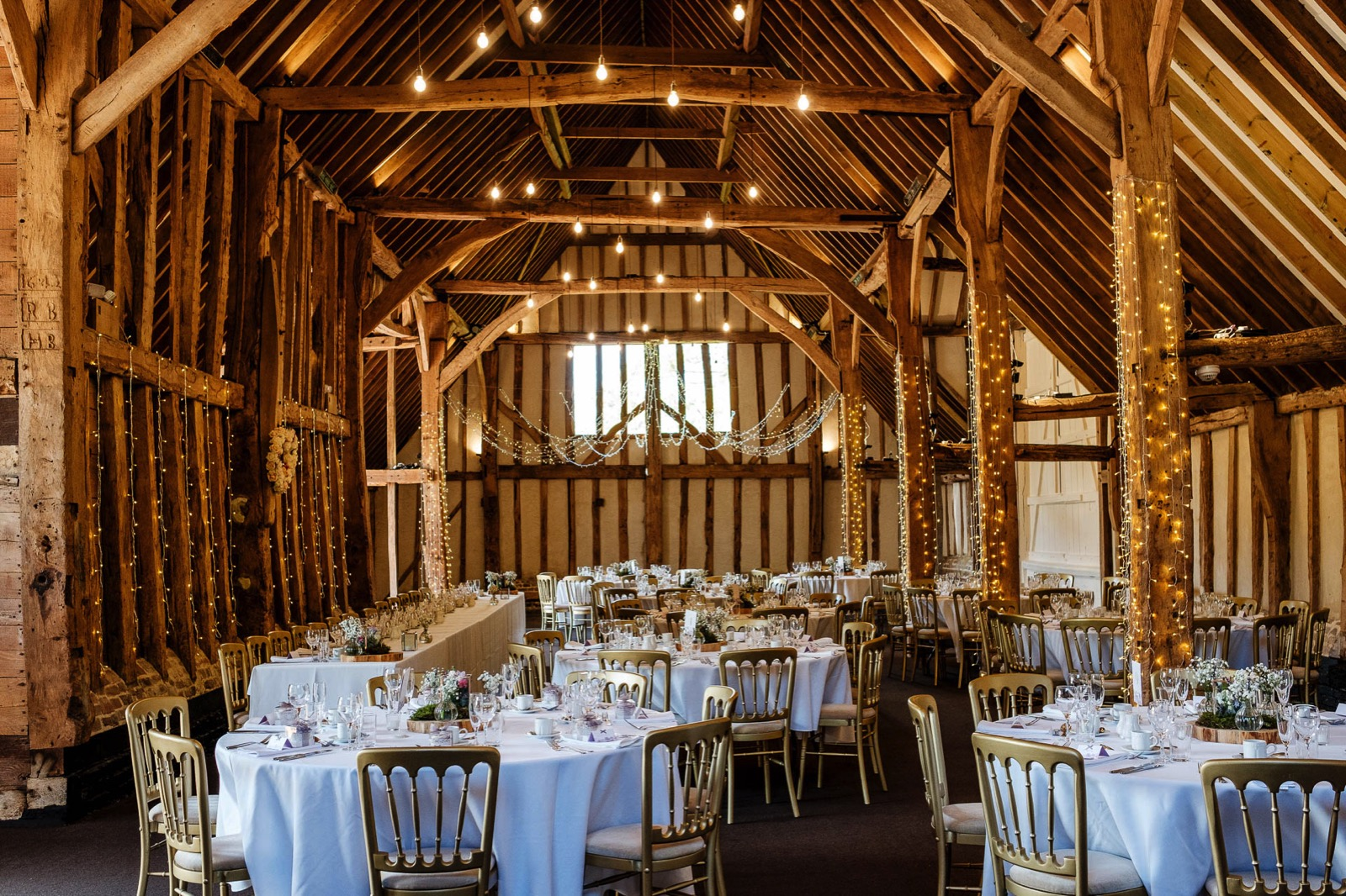 Photograph of the inside of the Barn at Wedding Venue Blake Hall in Ongar, Essex lit up with fair lights and tables with gold chairs