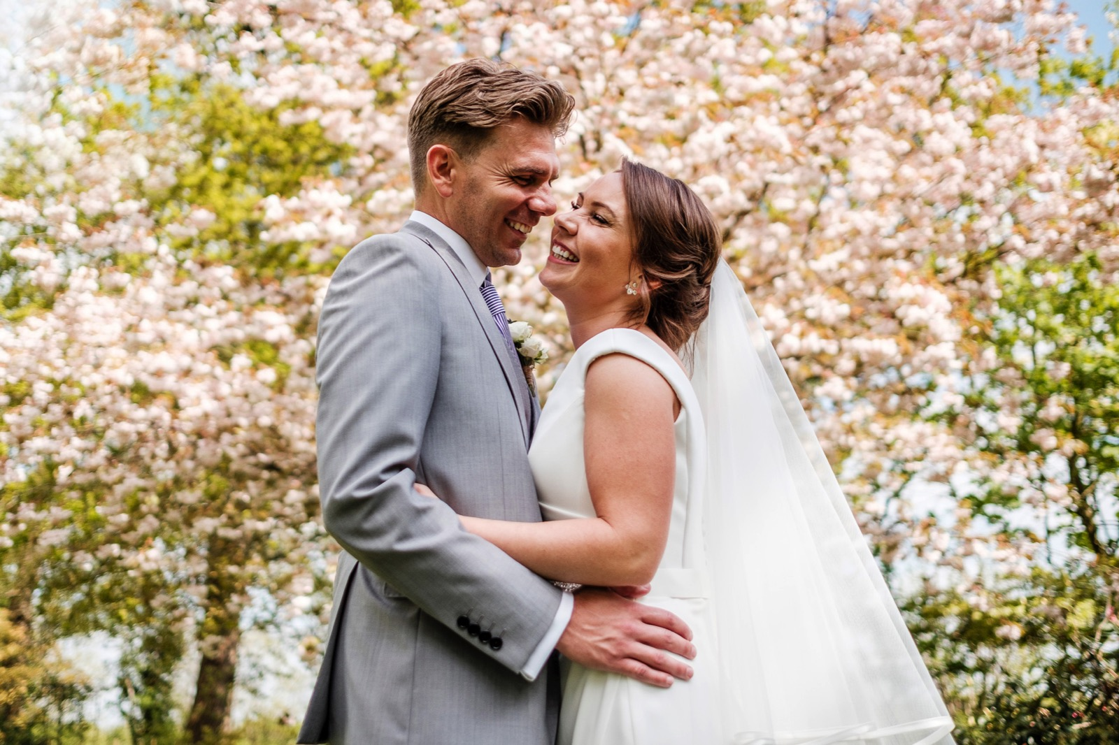 Bride & Groom laughing and embracing in front of trees covered in stunning white blossoms