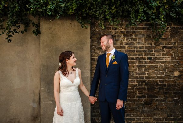 Bride & Groom hold hands laughing during their portrait shoot at their Alternative East London Wedding at Holborn Studios