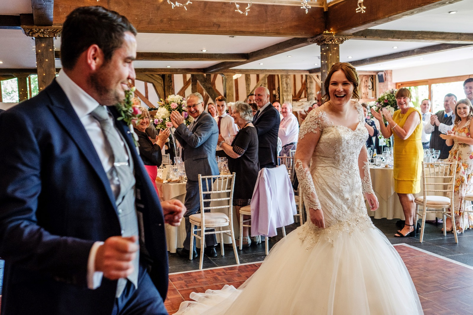 Bride & Groom laughing during their first dance as guests clap