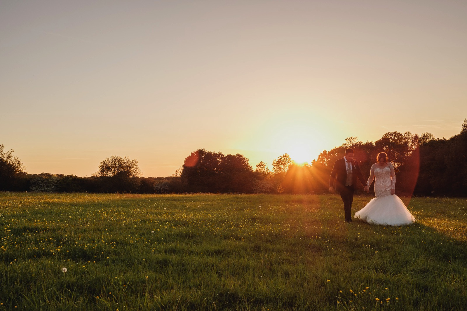 Newly married couple walking in the Grass fields as the sun sets on their Old Brook Barn Wedding