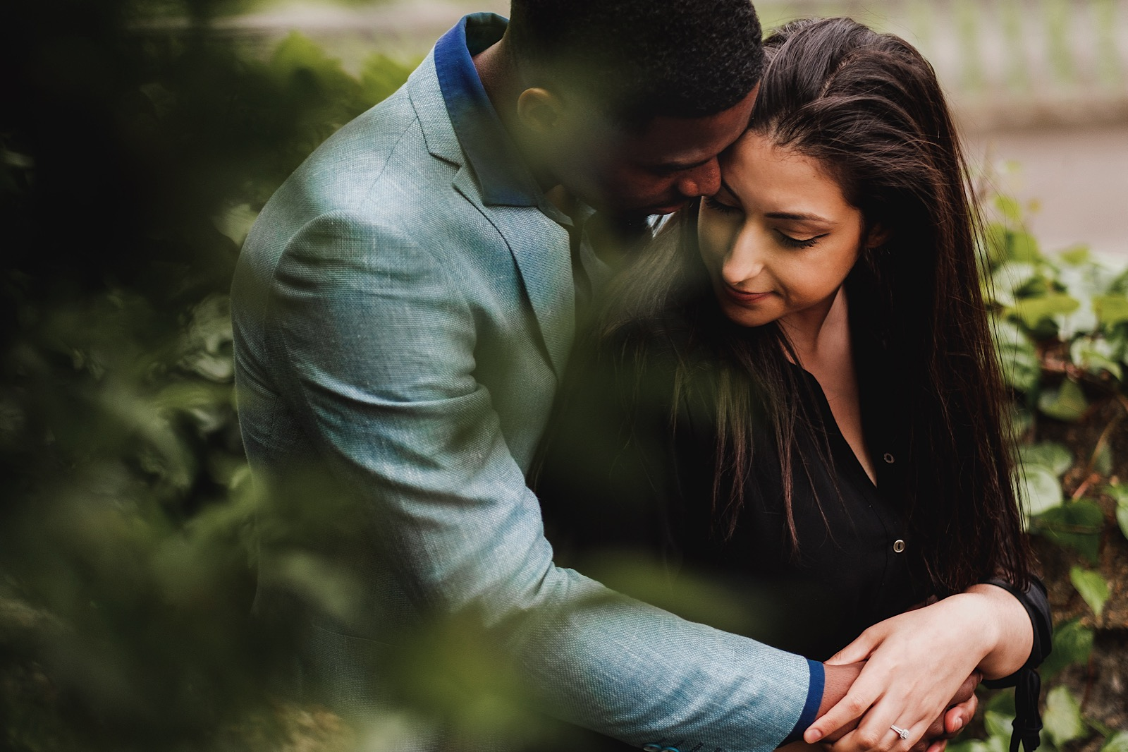 man embracing fiancee resting their heads together