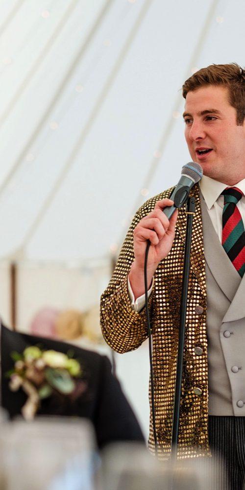 Best man giving wedding day speech dressed in shiny metallic gold sequin jacket