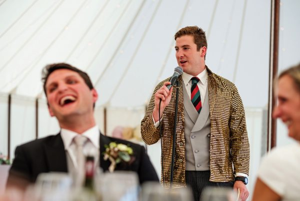Best man giving wedding day speech dressed in shiny metallic gold sequin jacket