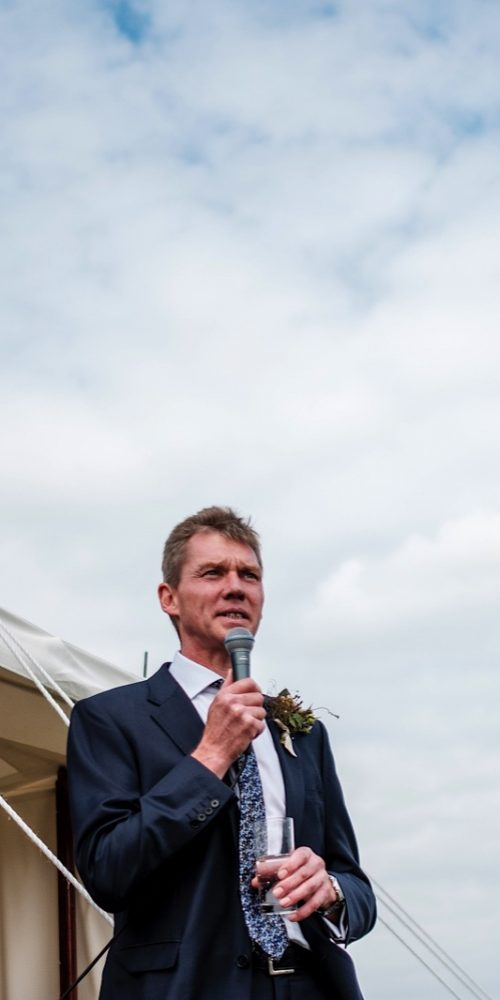 Gentleman wearing a blue jacket with blue patterned tie giving a wedding day toast outside a marquee using a microphone