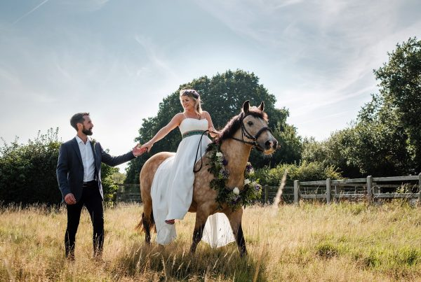 Bride riding horse that has a floral necklace with groom holding her hand alongside
