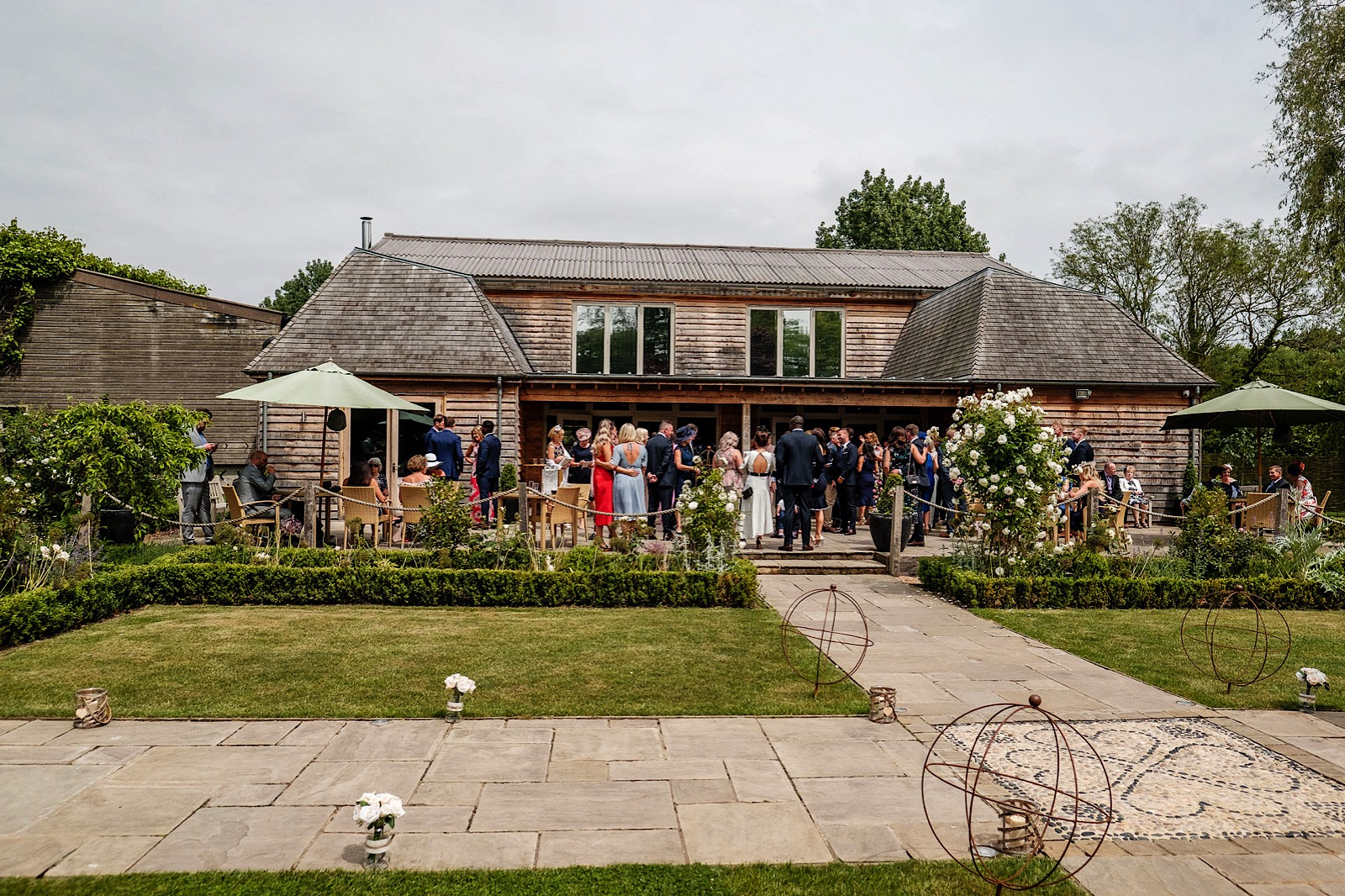 Photo of wedding guests waiting outside in the gardens of the Barn at Houchins Farm in Colchester Essex