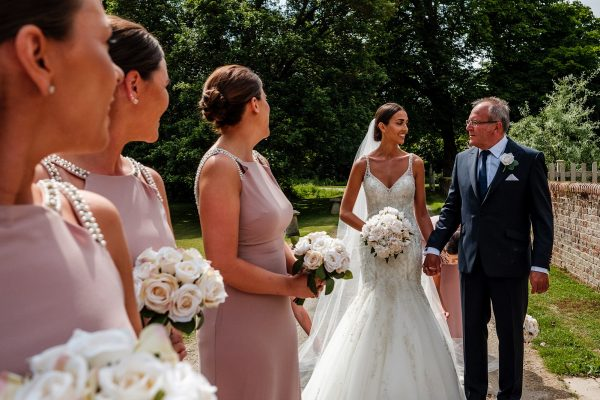 Bride being watched by bridesmaids as she walks hand in hand with her dad