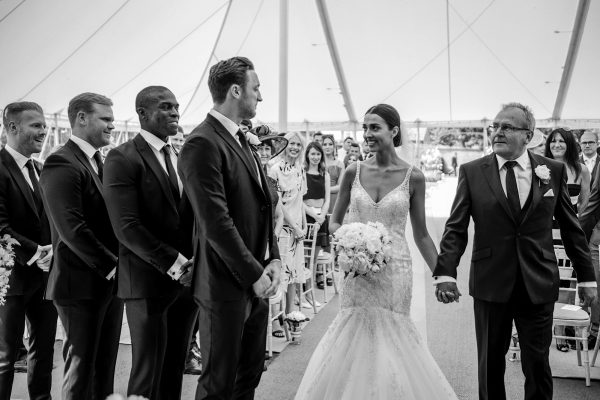 father of bride walking hand in hand with his daughter to her husband-to-be who is waiting with his best men