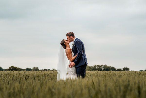 Bride & groom kissing in a wheat field
