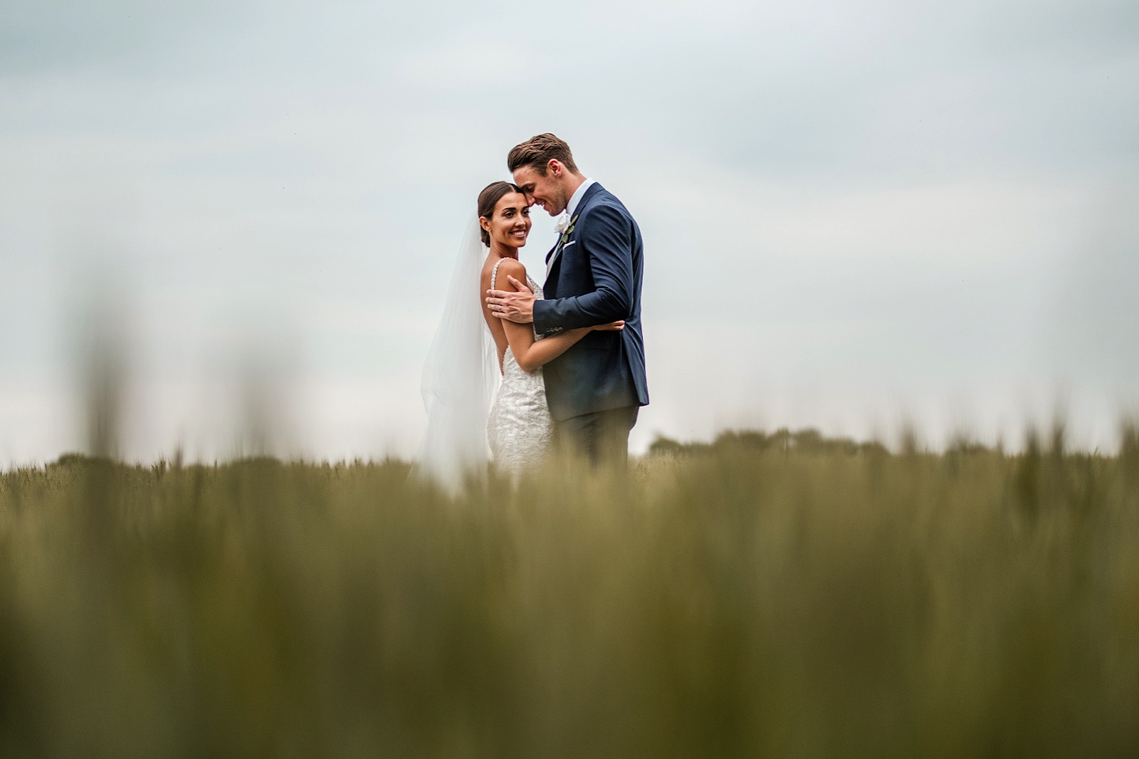 Bride & groom embracing in fields