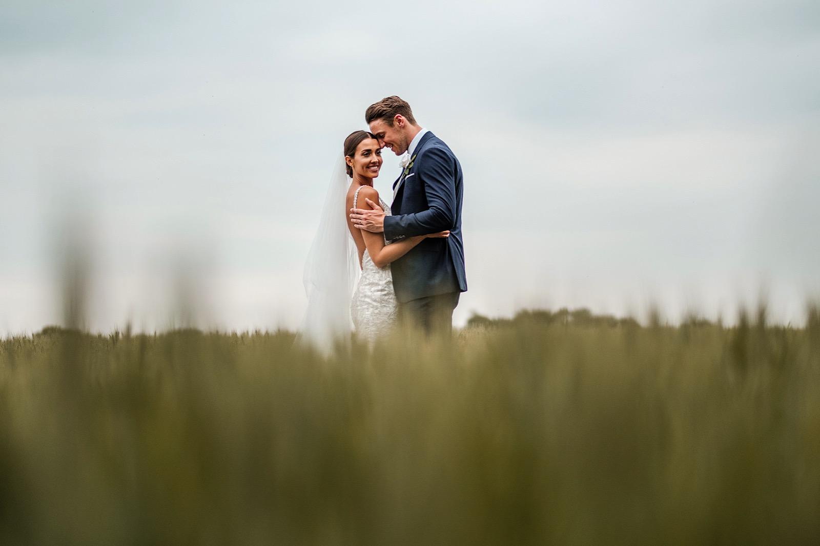 Bride & groom embracing in fields