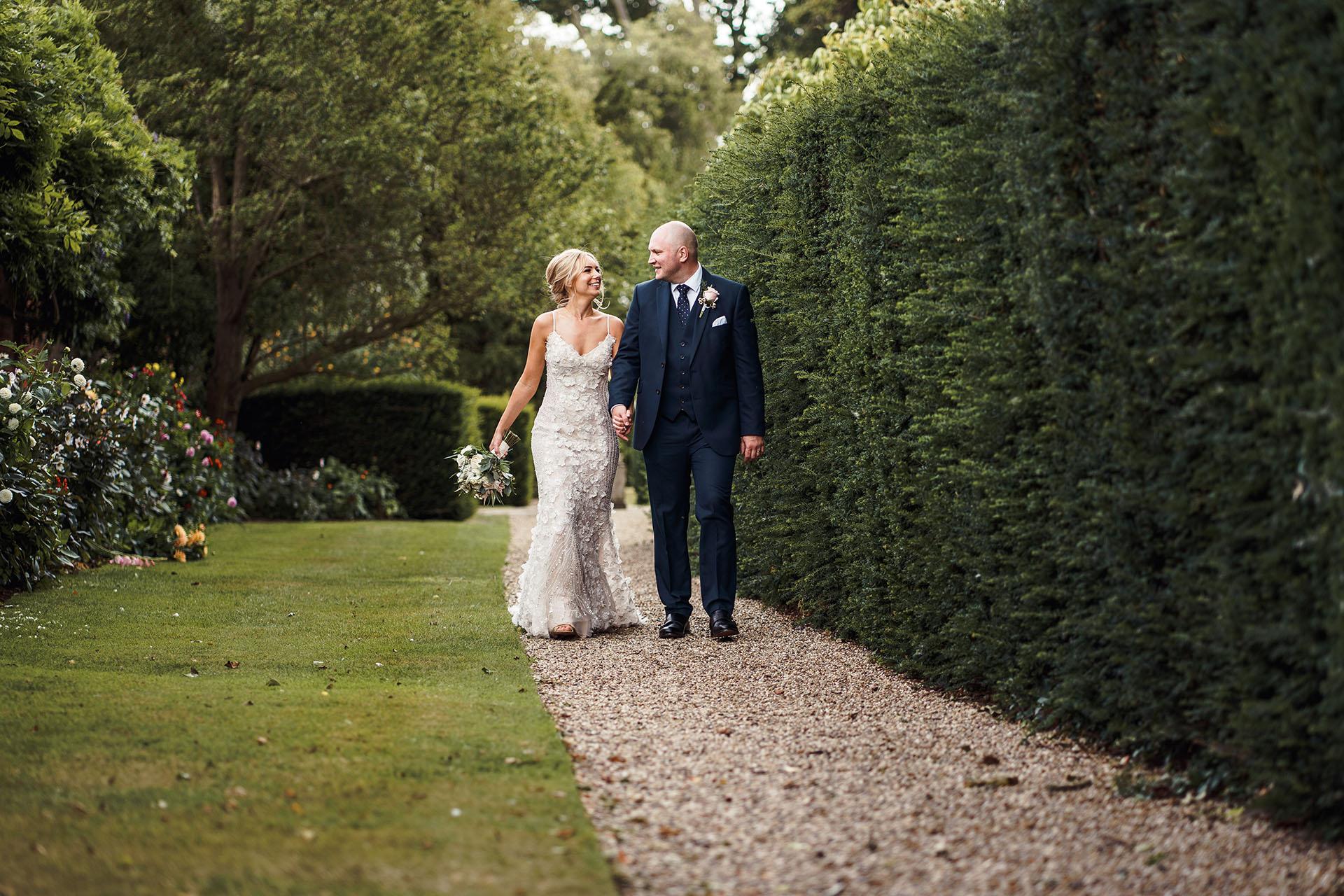 Bride and Groom walking through the gardens at Blake Hall Wedding venue