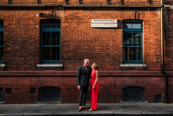 Man in suit with Fiancee wearing Red outfit stood outside of Winchester Walk in London for their sunset pre-wedding shoot