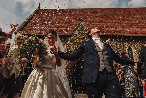 Bride & groom being showered with confetti outside of the church