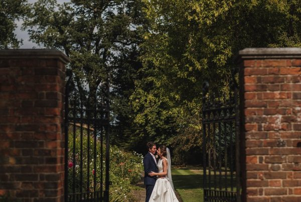 Bride and Groom captured between two cast iron gates at Blake Hall as they look into each others eyes