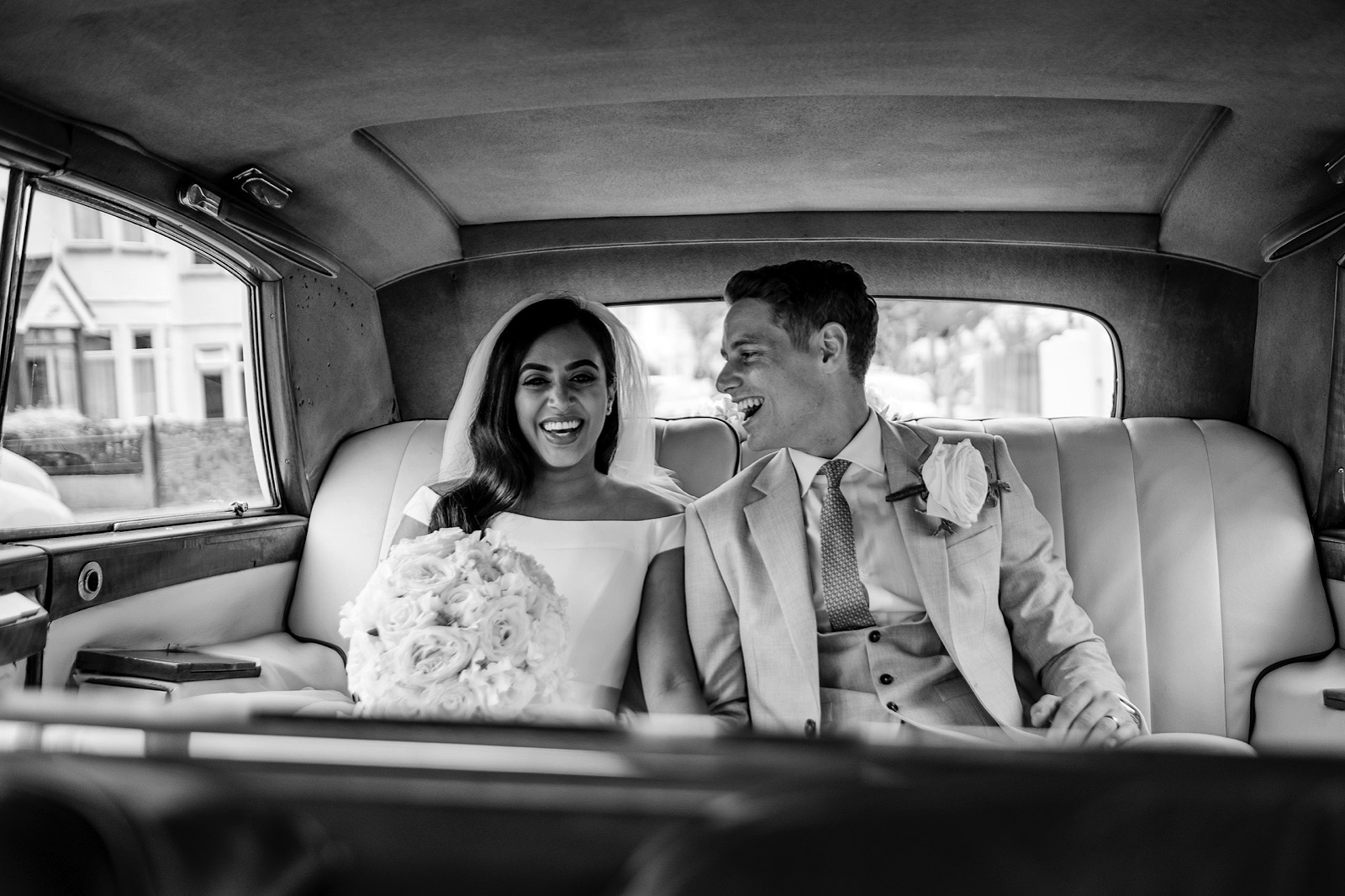Bride & groom sat in the backseat of wedding car laughing