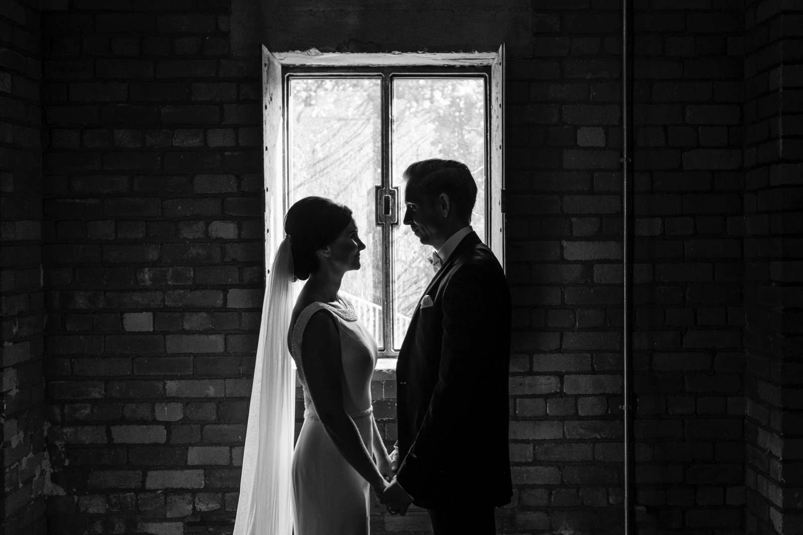Bride & groom stoof in industrial setting of Victoria Warehouse, Manchester backlit by a window