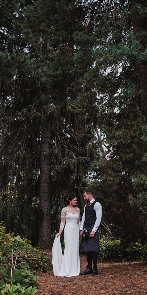 Bride & Groom stood next to giant trees in The Royal Botanical Gardens in Edinburgh