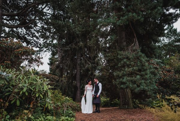 Bride & Groom stood next to giant trees in The Royal Botanical Gardens in Edinburgh