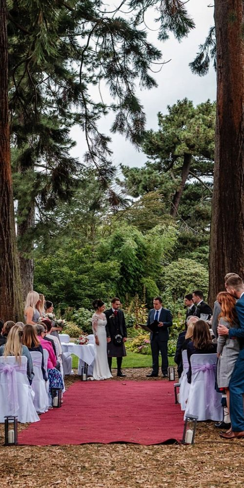 Couple having an alternative wedding ceremony outside under great trees