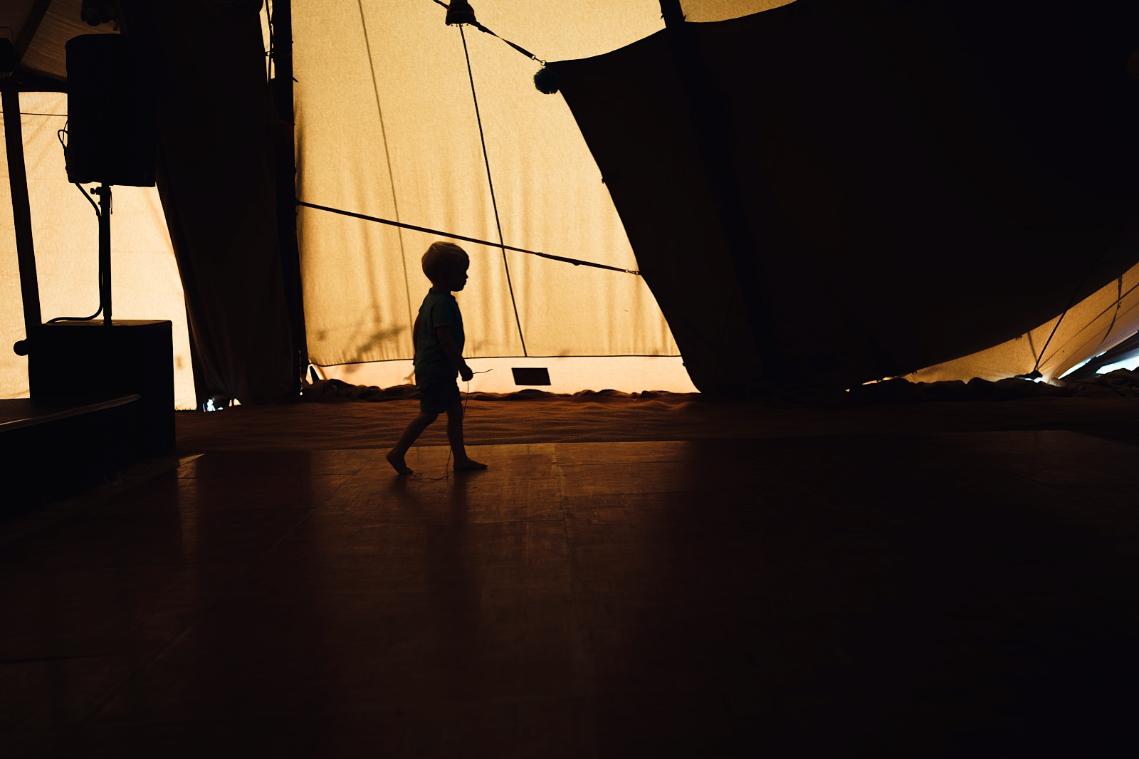 Silhouette of a child walking against the orange surface of a tipi during a wedding reception