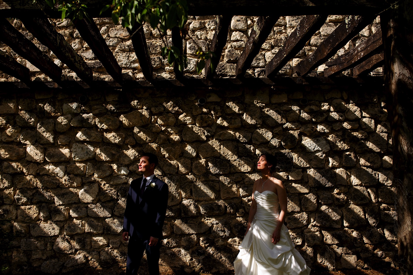 Creative portrait of a bride and groom with strips of sunlight subtly lighting their faces captured by a Street Photography Style Wedding Photographer
