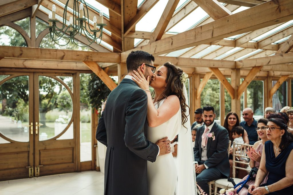 Bride and Groom having their First Kiss in the Orangery at Gaynes PArk