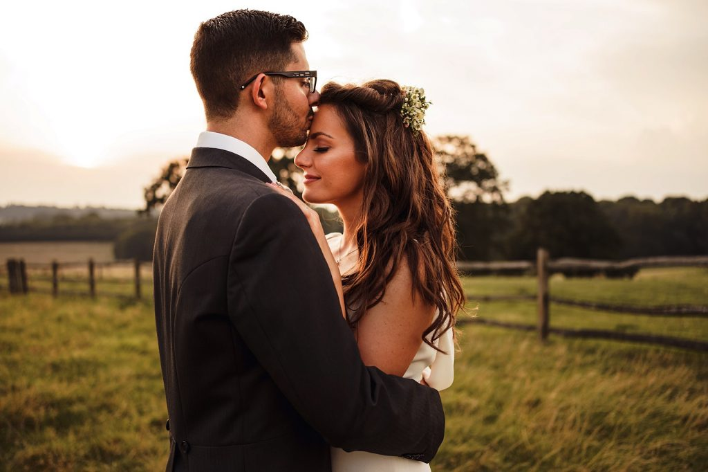 Groom kissing his bride on the head