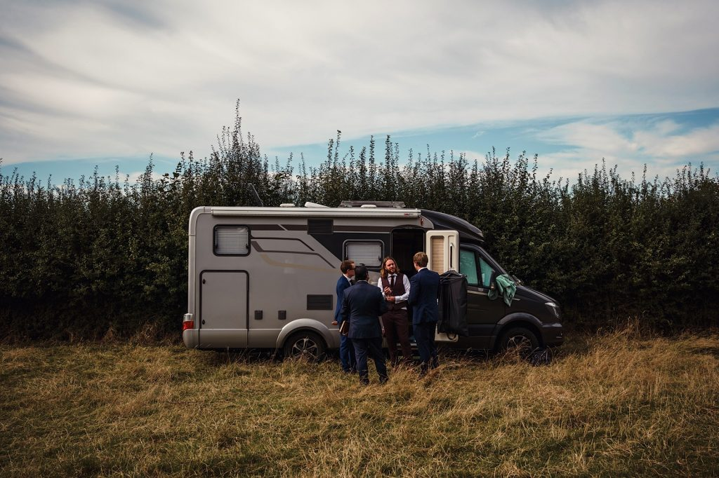 Groomsmen getting ready in a camper van in the middle of a field