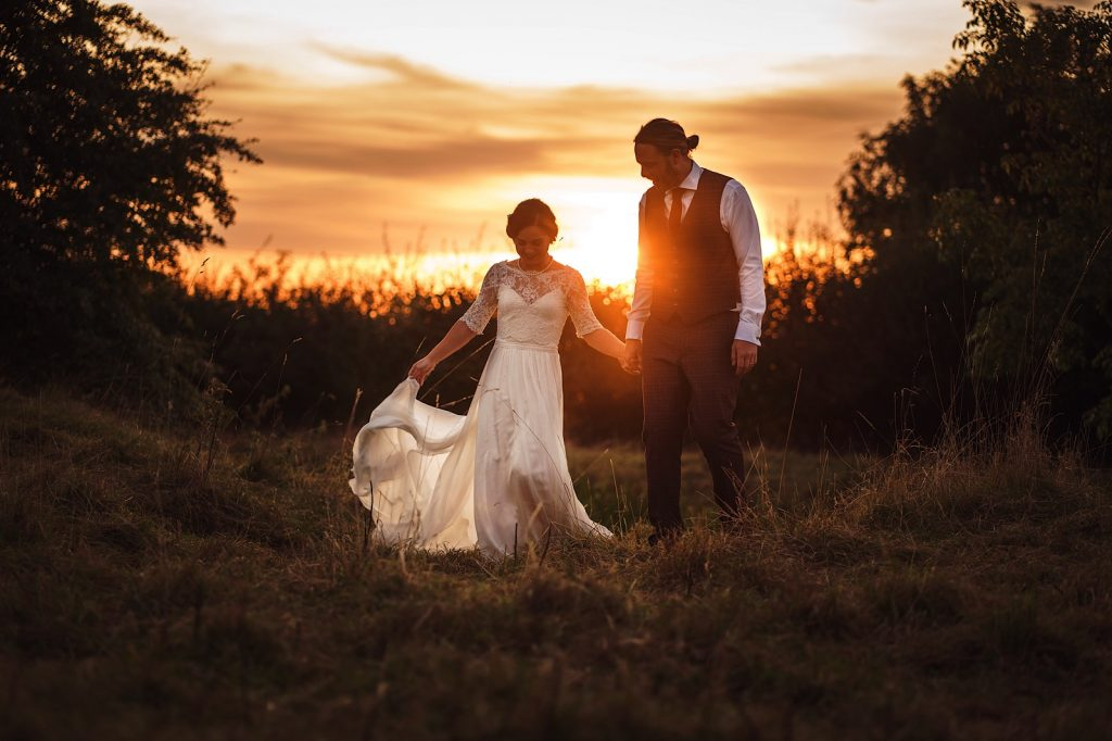 Bride and Groom walking in the sunset during their Tipi Wedding