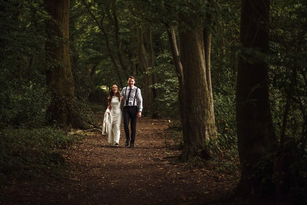 Bride and Groom walking through the forest smiling
