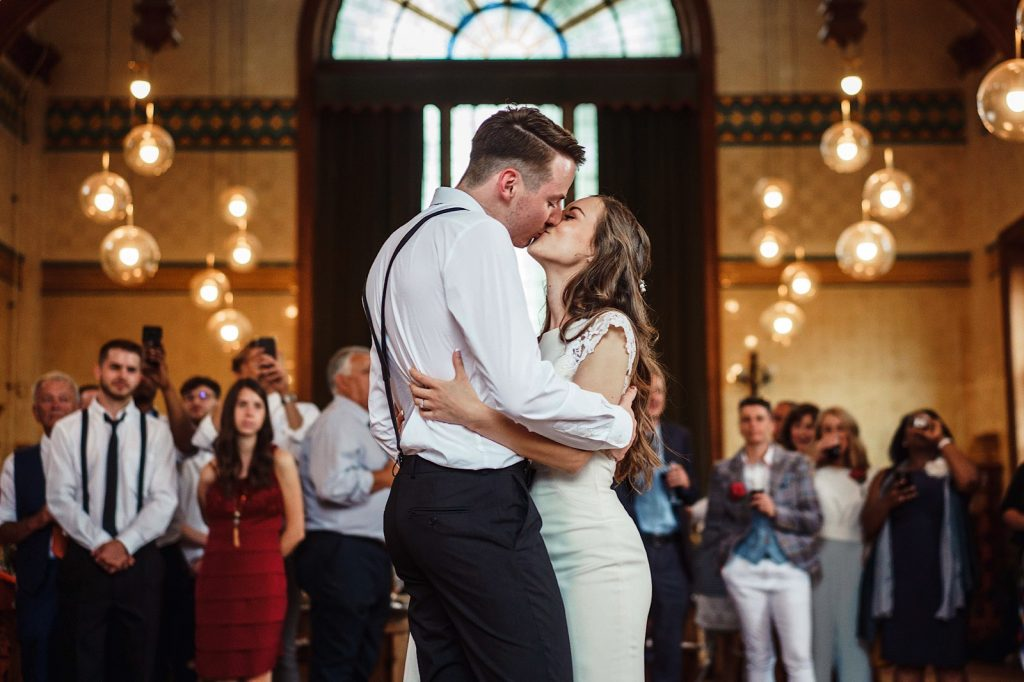 Beautiful moment during the first dance with the bride and groom kissing.