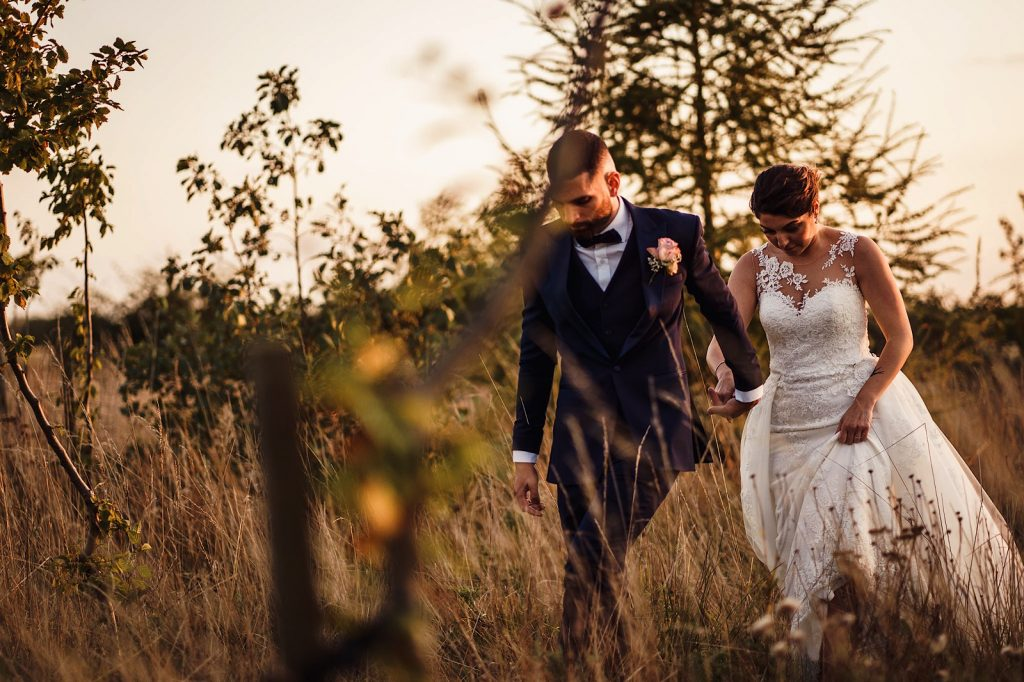 Bride and Groom walking through a meadow