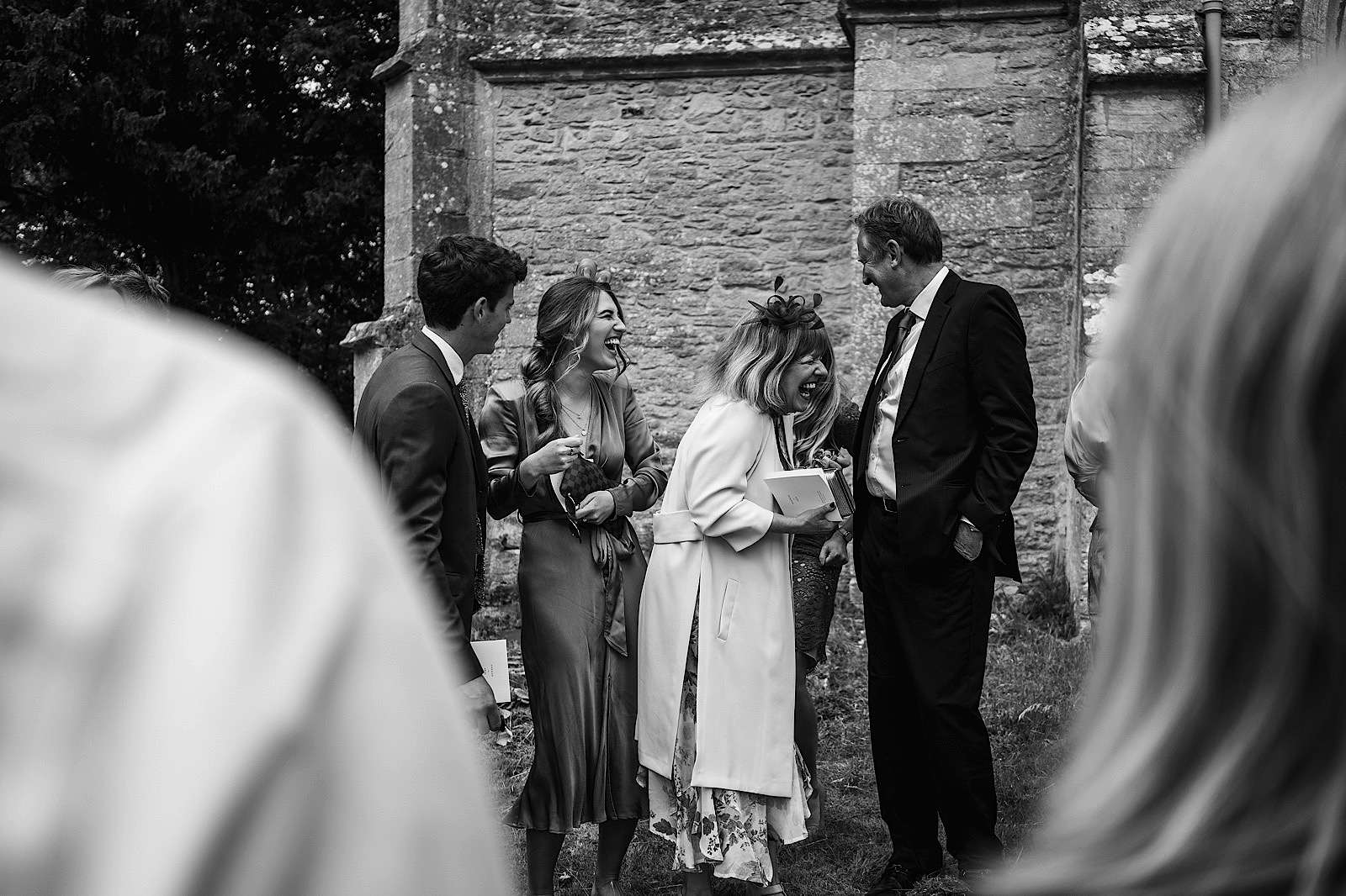 Documentary wedding photographer capturing a moment of guests laughing at the church