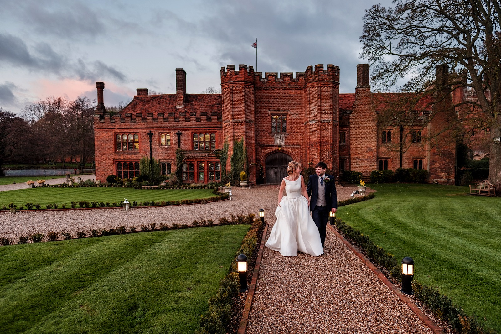 External view of Essex Wedding Venue Leez Priory with couple walking down a path